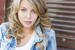 有大嘴唇的美丽的滑稽的白肤金发的女孩有一件迷人的微笑,佩带牛仔裤和一件白色衬衣的走在城市solnetsnym的 库存照片