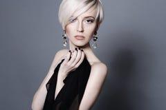有大水晶耳环的可爱的年轻白肤金发的妇女 免版税图库摄影