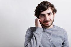 有大黑眼睛现代发型的穿偶然灰色毛线衣听音乐或audiobook的年轻行家和胡子与h 图库摄影