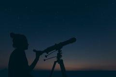 有天体望远镜的妇女 繁星之夜星座, 免版税库存图片