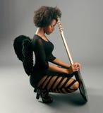 有天使翼和电吉他的美丽的黑人女孩 免版税库存图片