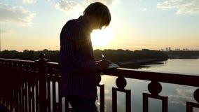 有天才的人在桥梁站立并且写他的想法下来在日落在slo mo 影视素材