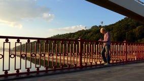 有天才的人在河桥梁站立并且投入他的想法下来在日落 股票录像