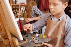 有天才的男孩绘画在艺术学校 库存图片