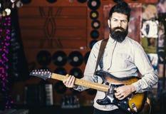 有天才的音乐家,独奏者,歌手在音乐俱乐部的戏剧吉他在背景 有胡子戏剧电吉他的音乐家 免版税库存照片