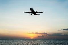 有天空日落和海的飞机 免版税图库摄影
