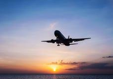 有天空日落和海的飞机 库存图片