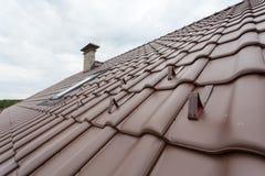 有天窗、自然红色瓦片和烟囱的屋顶有雪stopers的 免版税库存图片