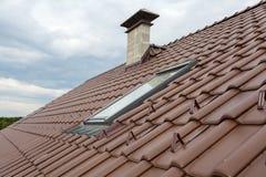 有天窗、自然红色瓦片和烟囱的屋顶 库存图片