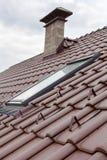 有天窗、自然红色瓦片和烟囱的新的屋顶 免版税库存照片
