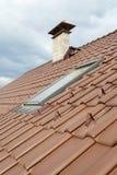 有天窗、自然红色瓦片和烟囱的新的屋顶 库存照片