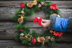 有天蓝色的温暖的夹克袖子的妇女手在欢乐圣诞节花圈附近 免版税库存图片