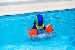有太阳使用在儿童的水池的保护衣物的男孩 库存图片