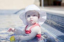 有太阳保护的美丽的愉快的传神白肤金发的女孩小孩在水池 图库摄影