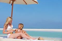 有太阳化妆水的母亲保护的女儿在海滩假日 图库摄影