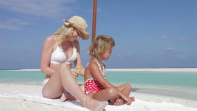 有太阳化妆水的母亲保护的女儿在海滩假日 股票视频