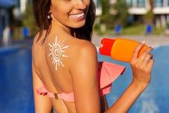 有太阳图画形状的女孩从遮光剂化妆水 免版税库存照片