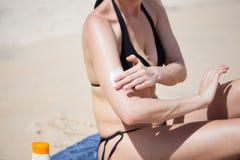 有太阳奶油的妇女在海滩 库存照片
