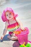 有太阳帽子的女婴在使用在海滩的沙子 图库摄影