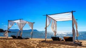 有太阳懒人的海滩机盖在海滩 免版税库存照片