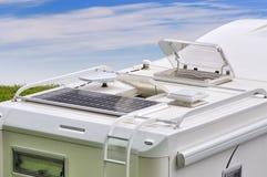 有太阳电池板、天线、oblo和梯子的野营车屋顶 免版税库存照片