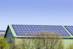 有太阳电池板的谷仓在屋顶和蓝天 免版税库存图片