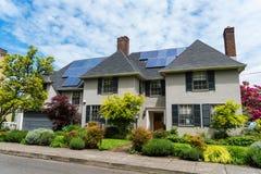 有太阳电池板的高级两层灰泥房子在屋顶 库存图片