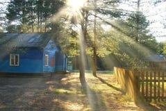 有太阳的蓝色木村庄房子 免版税库存图片