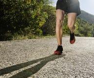 有太阳的赛跑者腿在森林公路点燃 图库摄影