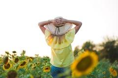 有太阳的年轻时尚妇女在时髦的帽子和蓝色牛仔裤短裤开花和 免版税库存照片