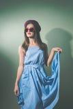 有太阳镜和帽子的美丽的典雅的女孩在轻的背景 免版税库存图片