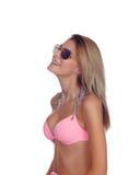 有太阳镜和桃红色比基尼泳装的可爱的时尚妇女 免版税图库摄影