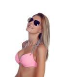 有太阳镜和桃红色比基尼泳装的可爱的时尚妇女 库存照片