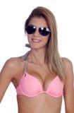 有太阳镜和桃红色比基尼泳装的可爱的时尚妇女 免版税库存照片