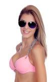 有太阳镜和桃红色比基尼泳装的可爱的时尚妇女 库存图片
