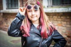 有太阳镜和皮夹克的微笑的女孩 免版税库存图片