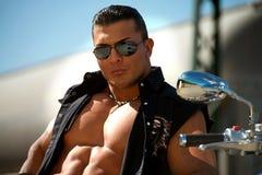 有摩托车的强壮男子的人 免版税库存照片