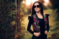 有太阳镜和花卉背心的时尚妇女 免版税图库摄影