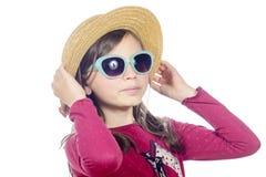 有太阳镜和草帽的一个相当小女孩 免版税图库摄影