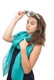 有太阳镜和蓝色围巾的美丽的青少年的女孩在她脖子摆在附近 免版税图库摄影