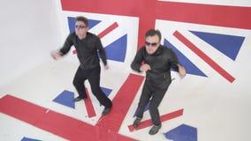 有太阳镜和黑皮革摩托车夹克的精力充沛的人跳舞 股票录像