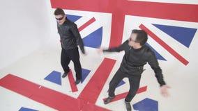 有太阳镜和黑皮革摩托车夹克的精力充沛的人跳舞 影视素材