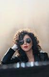 有太阳镜和黑皮夹克的迷人的年轻卷曲深色的妇女对墙壁 性感的华美的少妇 库存照片