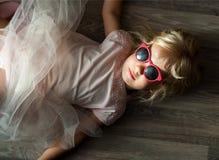 有太阳镜的一个小逗人喜爱的白种人女孩在地板上说谎 库存照片