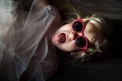 有太阳镜的一个小逗人喜爱的白种人女孩在地板上说谎 免版税图库摄影