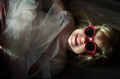 有太阳镜的一个小逗人喜爱的白种人女孩 免版税库存照片