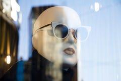 有太阳镜的一个时装模特玩偶显示了n最大玛拉衣物昂贵和典雅的品牌商店窗口与城市光的 库存照片