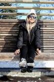 有太阳镜的与雪的女孩在冬天衣裳和起动 库存照片