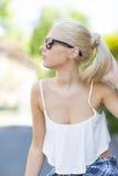 有太阳镜的偶然白肤金发的女孩在阳光下 免版税库存照片