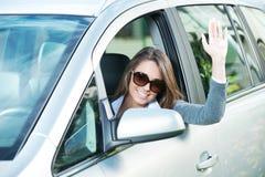 有太阳镜的可爱的妇女在她的汽车 库存图片